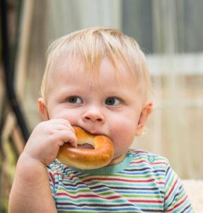 Мальчик ест бублик
