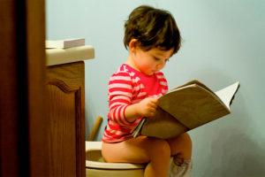 Ребенок сидит на горшке и читает книжку