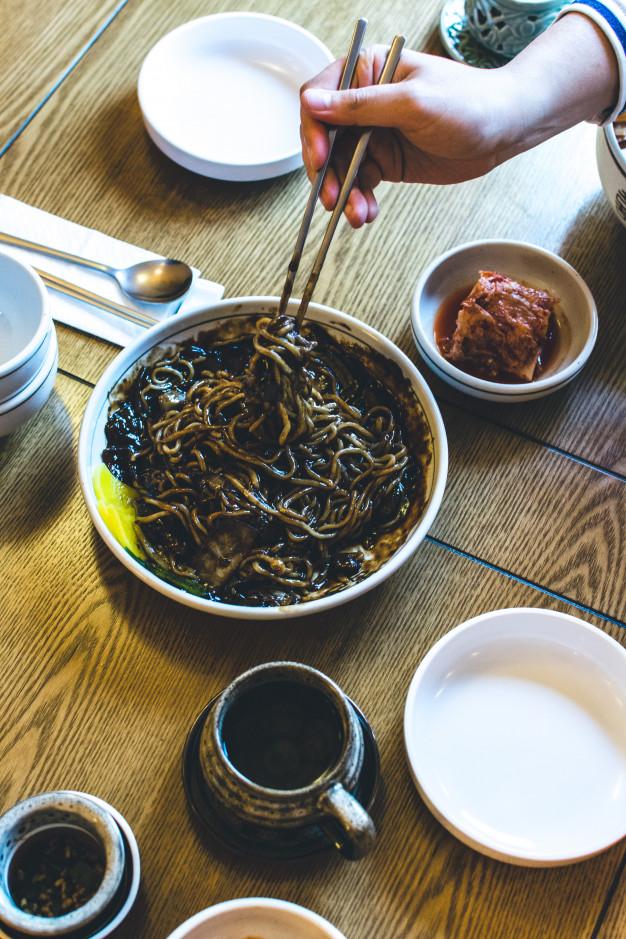Мужчина ест корейскую лапшу в толстом сладком соевом соусе с ...
